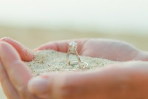 wedding ring on palm hand and sandy sand