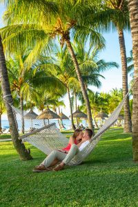 couple on hammock having a romantic time together under the beautiful coconut tress and the amazing mauritius sunny day
