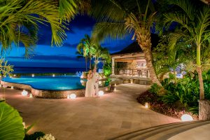 mauritius honeymoon photographer taking picture of couple in front a nice swimming pool at dawn with coconut trees