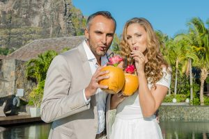 couple drinking cocktail into a coconut decor before wedding ceremony starts