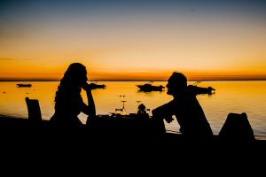 silhouette of couple having diner by the seaside