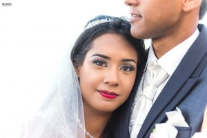 bride with red lips stick and a light make-up seems to be very happy in the arms of her husband