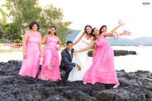 fun shoot by the beach for the couple and their bridesmaid who are wearing a pink dress