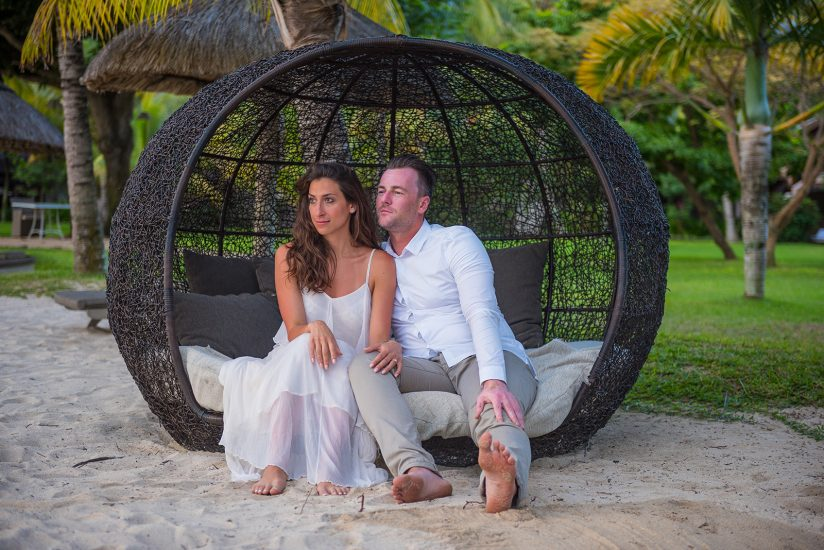 Couple sitting on a round sofa by the seaside