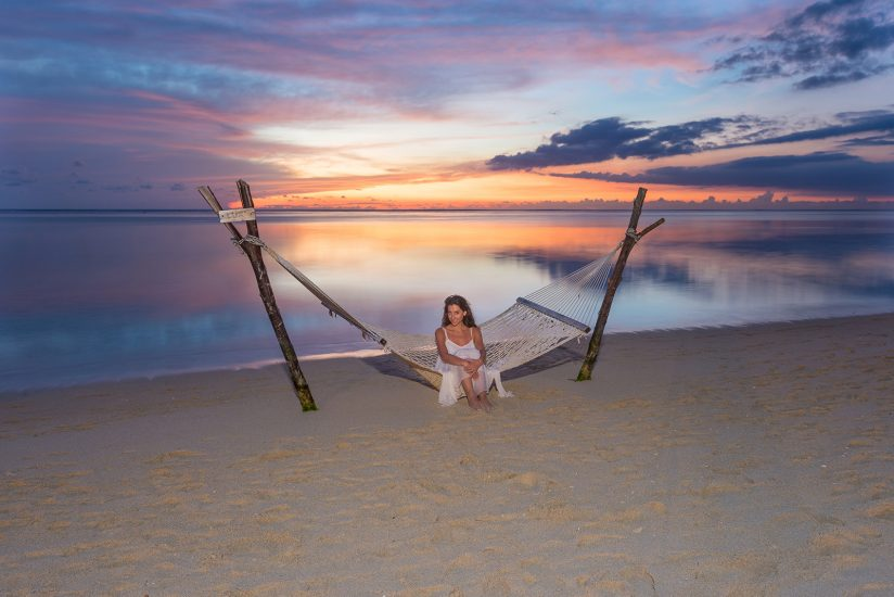 bride sitting on a Hammock by the seaside with an awesome sunset