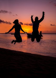 silhouette of two people jumping by a sunset