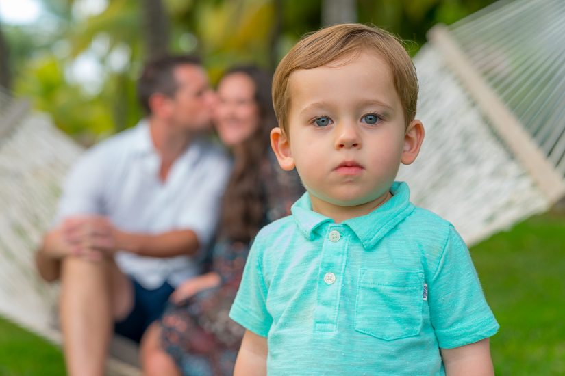cute little boy infront of camera while parents are in the background