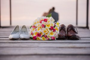 bridal shoes, bridal bouquet and groom shoes left on on jetty