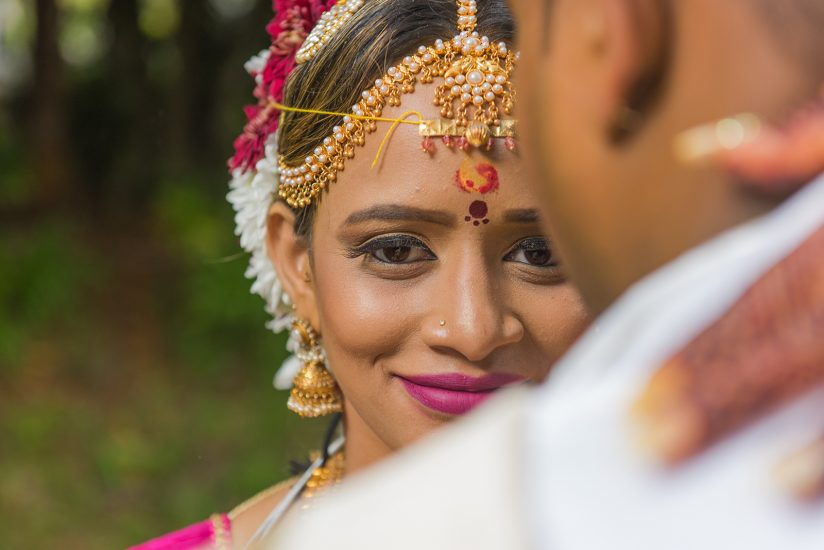 Tamil bridal holding the neck of her man while shes looking at the camera with a beautiful smile and eye contact
