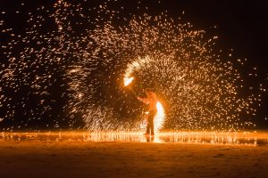 man playing with fire by a seaside