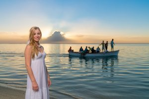 bride posing while fishermen are on their boat